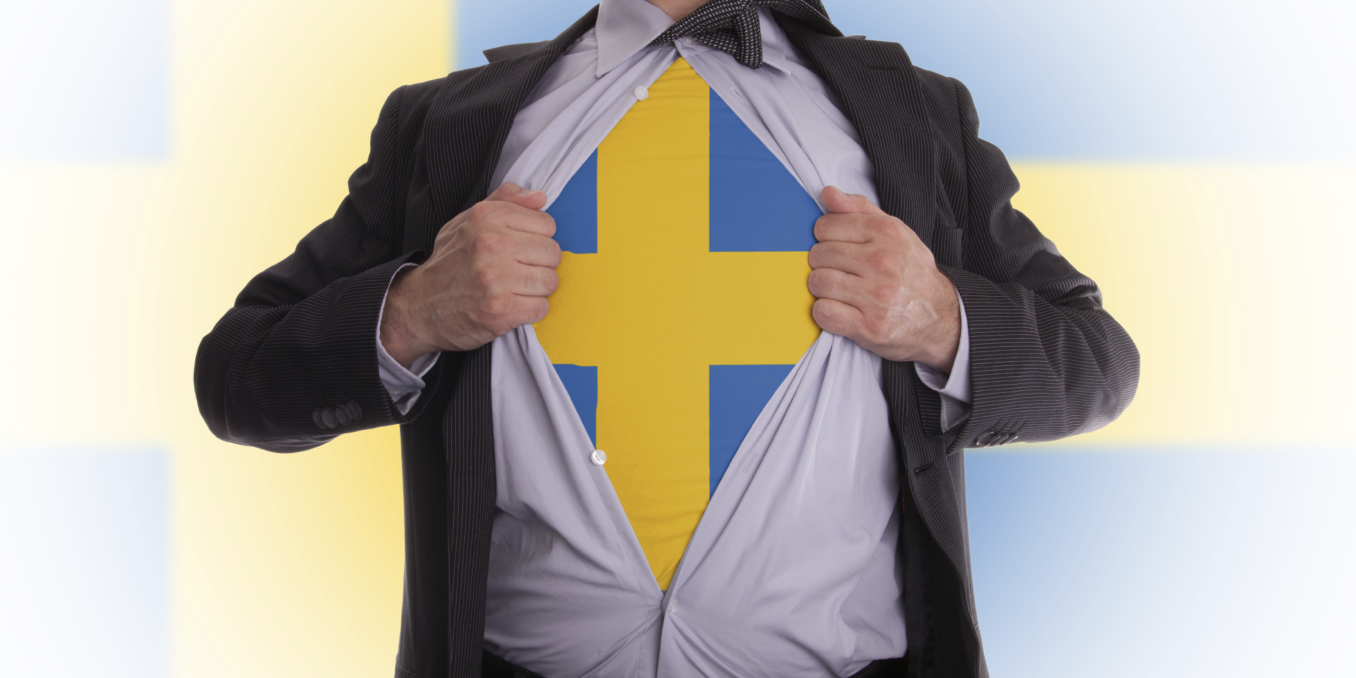 Business man rips open his shirt to show his Swedish flag t-shirt