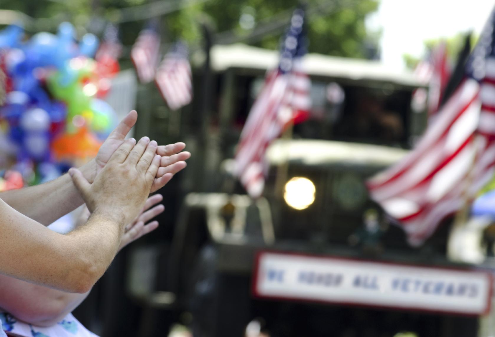 closeup of hands clapping at veterans parade