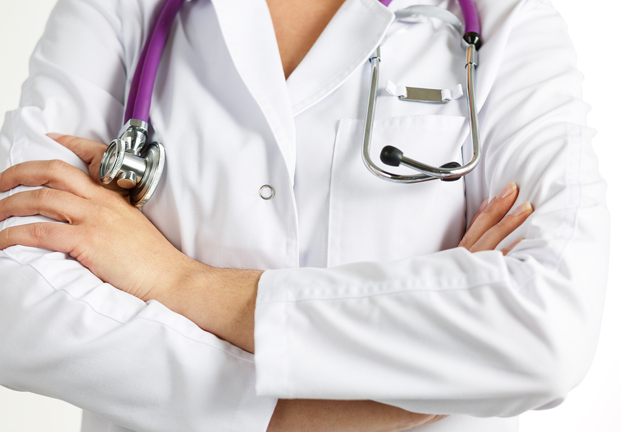 Female medicine doctor standing with hands crossed on her chest closeup. Medical help or insurance concept. Doctor is waiting for patient to examine. Physician reception concept